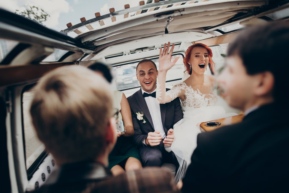 a couple and their wedding party celebrate in the back of a bus