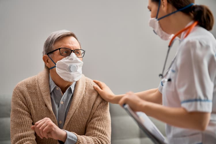 Nurse comforting old man, both wearing masks