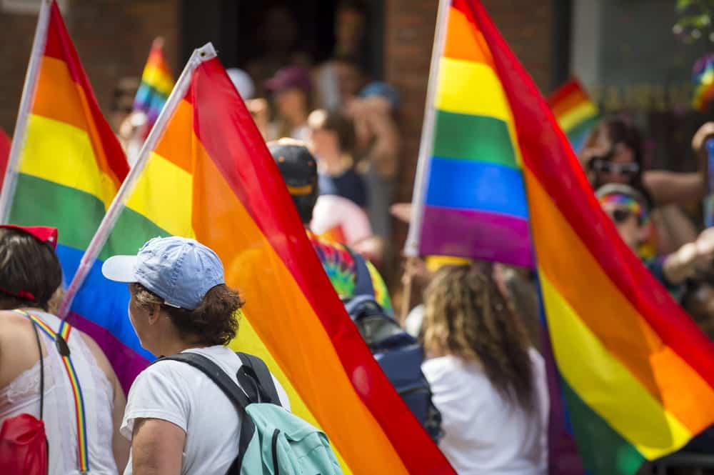 People marching with rainbow flags in NYC Pride parade
