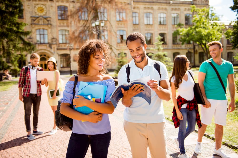 students smile and look at textbooks on a los angeles university campus