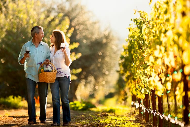 Couple walking in vineyard sipping glasses of wine.