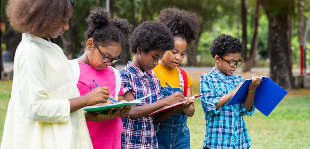 children writing in notebooks on a field trip