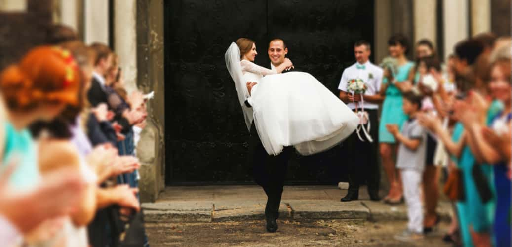Bride being carried by groom with wedding guests clapping
