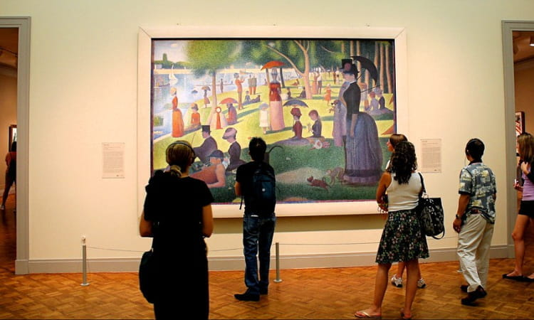 visitors gather to view a famous painting at the art institute