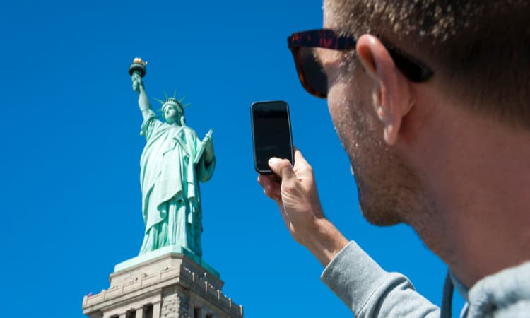 man taking a photo of the statue of liberty with a smart phone