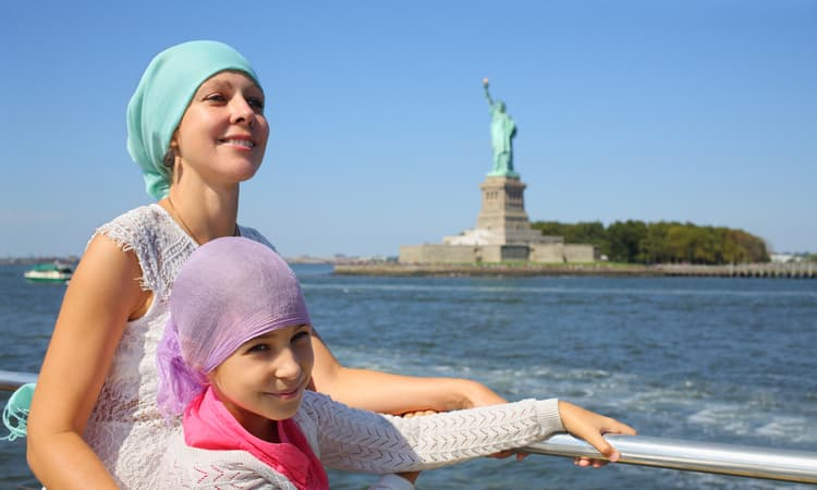 mother and daughter on ferry with statue of liberty behind them