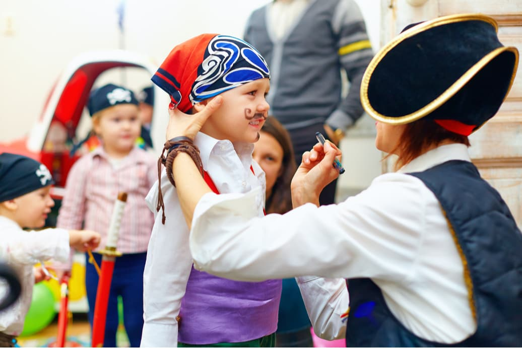 someone dressed as a pirate paints a child's face with a mustache