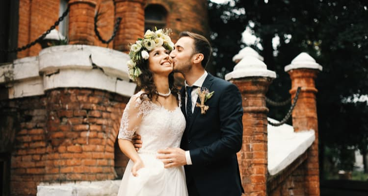 wedding couple embracing outside a brick building