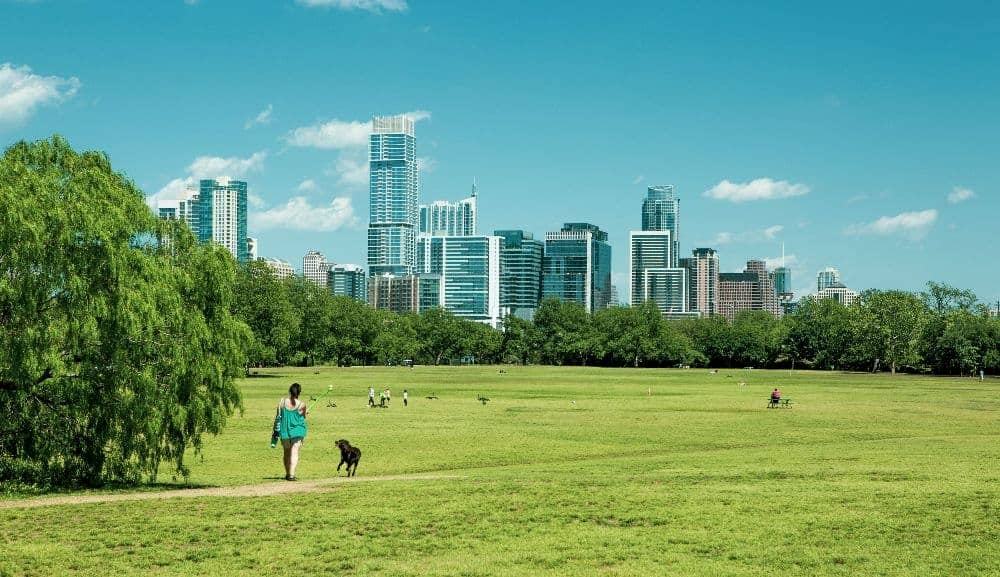 a girl and her dog wander zilker park in austin